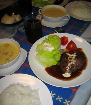 青いランチョンマットに、白い大きめのお皿にハンバーグと、レタス、そしてカットされたミニトマトが盛られています。やや小さめの白いお皿にはライスが。やはり白いスープカップに黄色いスープが入っています。