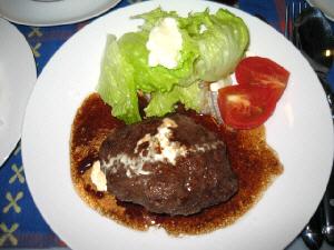ハンバーグの盛られたお皿のアップ画像。茶色いソースにハンバーグの上にたらされた白い生クリームの色が映え、見た目は美味しそうに見えます。レタスの緑、トマトの赤が、地味なハンバーグの色を引き立てています。