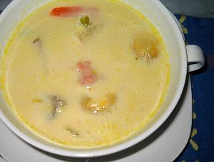 スープのアップ画像。白いカップソーサーと白いカップスープ。スープの優しい黄色実が食欲をそそります。