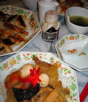 テーブルに同じ模様のお皿が3種。大皿にはこんがり焼き色のついた餃子が、中皿にはトッピングに紅しょうがが乗った中華丼が、一番小さいお皿は餃子のタレを入れる皿のようです。同じ模様のレンゲも添えてあります。真ん中にラー油と醤油が、ちらっと白いスープの小鉢も見えます。