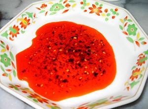 小花が散りばめられた縁取りの中華小皿。中にラー油が注がれ、色が真っ赤です。ところどころ見える黒っぽい粒は、唐辛子やその他のスパイスのようです。