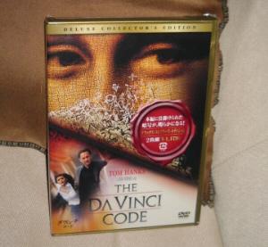 ダ・ヴィンチ・コードのDVD。モナリザの目の部分が表面上部いっぱいに描かれていて、主演のトム・ハンクス、助演のオドレイ・トトゥの二人が美術館を走り抜けている図柄が下端の方に描かれたパッケージです。