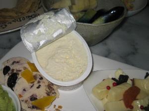 楕円形の器に入った白いチーズ。今開封したばかりのようです。向こう側には、茄子のお新香や大根のお新香が入った器も見えています。