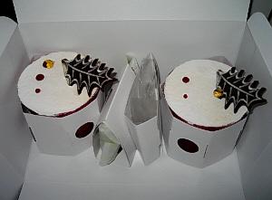真っ赤なカップなんですが、まだ白いボール紙で包まれている。カップの口にクリームが平らになるようにデコレートされているので、まるで真っ白なケーキのように見えています。もみのきを模ったチョコがトッピングされています。