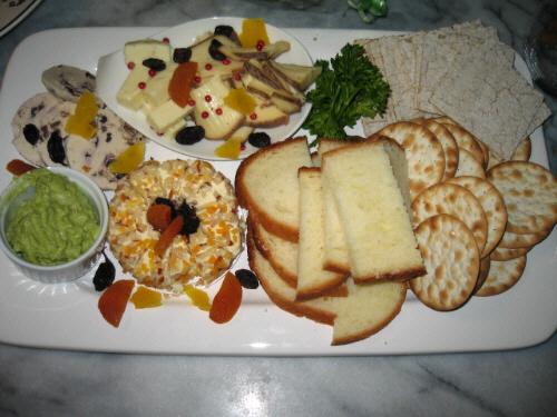 白い大きな四角のお皿に盛られたチーズや、クラッカー数種とパン等。フルーツの粒が沢山付いた丸いチーズ、スライスしたチーズ、数種類のチーズが乗っかっています。ところどころに散らしたドライフルーツやピンクペッパーが華やかさを演出しています。