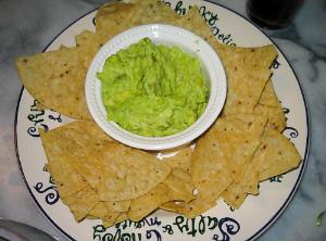 縁取りに英文が躍るように書かれた丸いお皿。真ん中に白いボウルが置いてあり、中にはたっぷりの緑色のペースト状のものが、その周りにはトルティーヤチップが並べられています。