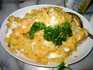 白い楕円形のお皿に山盛りになったポテトサラダ。赤く見えるのはサーモンのようです。トッピングにパセリが置いてありその緑が全体を引き締めています。