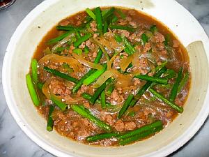 ニンニクの芽の炒め物が入ったグレーの和風のお皿。ひき肉と玉葱が緑のニンニクの芽に絡んでいます。