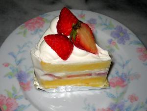 オーソドックスなイチゴのショートケーキ。うすい花模様の描かれたお皿の上に乗っています。