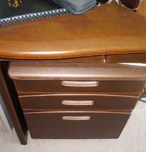 茶色い木目調の机、移動可能な引き出しが机の下に納まっています。