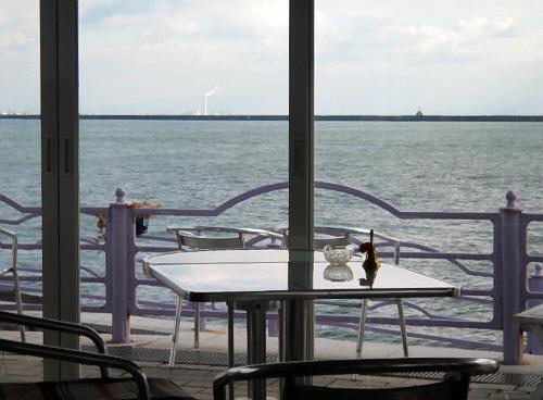 カフェのテラス席から外のテーブルや椅子が見え、すぐその向こうに海が広がっています。一部だけ切り取った様子は、まるで船のデッキから海を臨んでいるような雰囲気です。