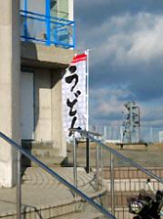 階段の手摺の向こうに「うどん」と書かれた幟が見えます。