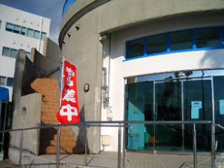 お店の入り口付近らしきところに、真っ赤な営業中と書かれた幟が立っています。ガラス越しに中はうどんを販売するカウンターが見えています。