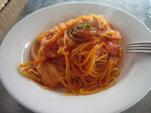 白い丸皿に盛られたパスタ。トマトソースが絡めてあり全体が赤い色です。