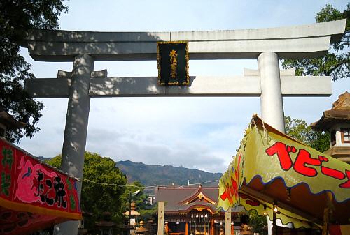 神社入り口の鳥居。入り口の前に2軒だけ出店がでていました。ベビーカステラとたこ焼きの垂れ幕が見えています。