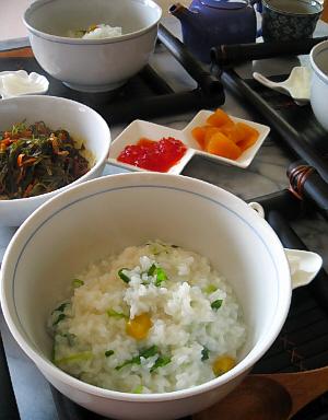黒い竹細工のお盆の上に白い丼に入っているお粥。緑色の葉っぱと黄色い銀杏が綺麗です。テーブルの中央には、筋子や残り物の数の子も並べられています。