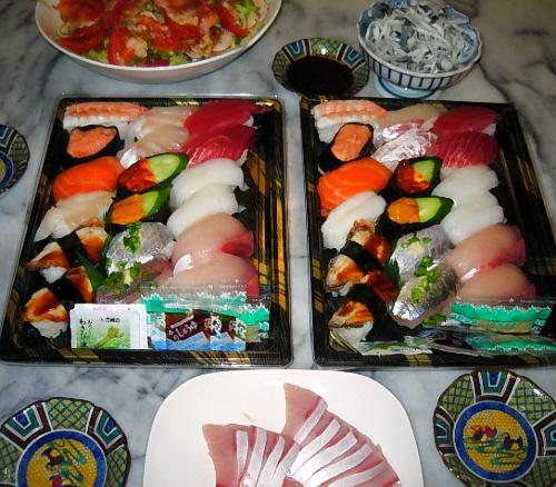 少し大きめのスチロールの入れ物に、並べられたお寿司、2パックが中央に置かれ、手前にブリのお刺し身が入った白いお皿、向こう側にフグの皮が盛られた小鉢、そしてサラダの入った大きめの白いボウルが。