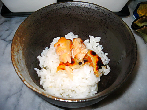 黒っぽいご飯茶碗の底のほうにちょっぴり白いご飯が、その上にシャケが乗っています。
