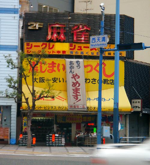 靴屋さんの屋根の部分に取り付けられた大きな黄色い看板、そこには「店じまい、売りつくし・大阪一安い店、うわさの靴店」と書かれています。その上に大きな垂れ幕が、それには「もうあかん、やめます」と大きな字で、下のほうには換金セールと書かれていますが、どちらも汚れの目立つ年季ものです。