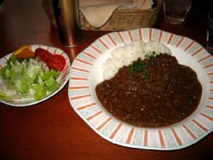 お揃いの大小のお皿に盛られたカレーとサラダ。ひき肉がたっぷりでお肉の粒がしっかり見えるカレーです。