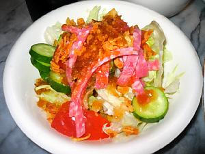 サラダのアップ画像。きゅうりの緑、トマトの赤、レタスとお皿の白。3色揃うとまるで国旗の色のようですね。茶色い粒々はフライドオニオン、茶色いソースはドレッシングです。