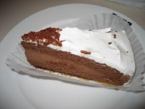 白いお皿に乗った三角形の茶色いケーキ、上には生クリームが塗られています。