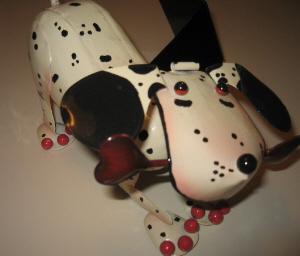 白いテーブルの上に、ブリキの犬のオモチャが飾られてあります。ダルメシアンのようですが、愛嬌のある顔をしていて、口には骨を咥えています。足にピンクの丸い球がついていて、指を表しているようですが、これがとってもキュートです。