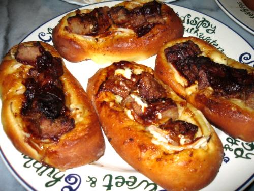 大皿にやや細長い楕円状のパンが4個。ハンバーグとソースが絡み合って美味しそうです。白っぽいのがチラッと見えるのはマヨネーズでしょう。