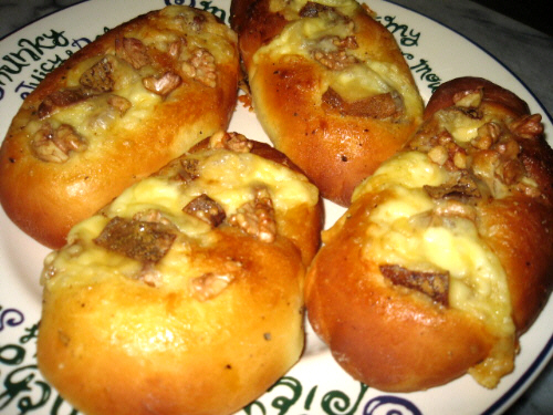 上と同じ形のパン。上に乗っているのは胡桃の粒と、とろりと溶け出したチーズです。程よく焼けたパンの色が香りまで想像させます。