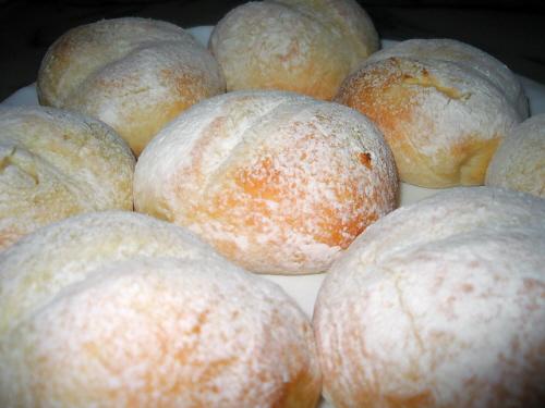 白パンのアップ画像。パンの上に散らした粉が、雪のように見えます。雪の下からちょっぴりキツネ色に焼けてしまったパンの地肌が見えているのは愛嬌です。