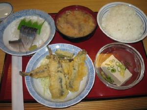 赤いトレーの上に、ご飯、豚汁、冷奴の入ったガラスの器、天ぷらの入った丸いお皿、それより少し小さめのお皿に、きずしが乗ったものが適当に並んでいます。