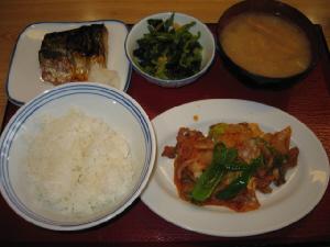 同じく赤いトレーの上に、ご飯、みそ汁、お浸しの入った小さな器、焼き魚の乗った四角いお皿、そして豚キムチの乗った白い丸皿、それにご飯と味噌汁が並んでいます。