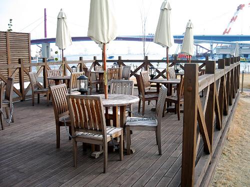 なぎさの湯の施設の一部のガーデンデッキ。もう少し温かくなったら、ここでのんびり海を眺めながら食事でもしたいものです。この日はパラソルは全部畳んであって、テラスを利用している人は皆無でした。木製のテーブルも椅子も寂しげな佇まいです。