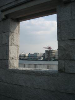 同じ四角い窓風の穴から外側を見た写真。川面と対岸のビルが絵画風に見えるようにしているのかも。