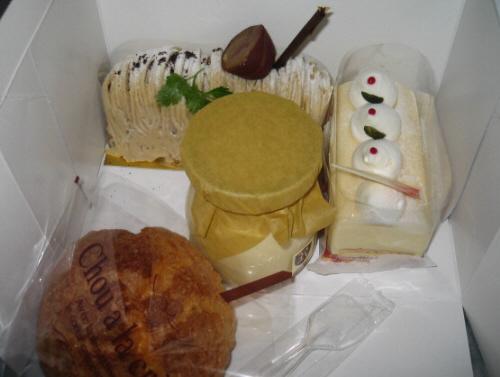 ケーキ屋さんの箱に入ったままのケーキとプリン。モンブラン風の長方形のケーキと、レアチーズケーキ、シュークリーム、そして小さなプリンの瓶が入っています。