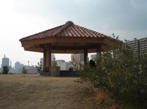海辺の高台に東屋のような赤煉瓦の屋根が見えていて、人が座っているようです。