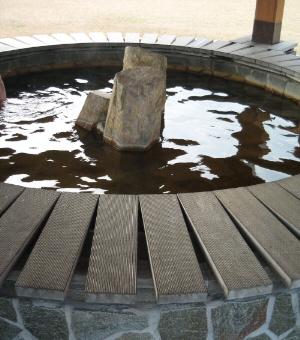 屋根の下は足湯になっていて、丸くベンチが作られ、のんびり足湯を楽しむ人たちが座っています。人は避けて足湯のお湯だけ写真に撮ってあります。