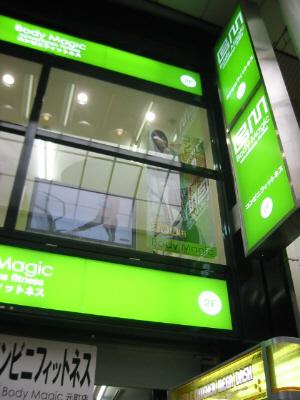 グリーンがアクセントのお店の看板。二階の窓のガラス越しに、マシンの大きなポスターが見えます。入り口には大きな字で、コンビニフィットネスと書かれてあります。