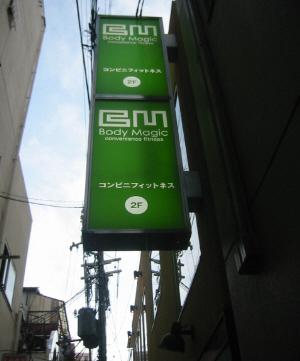 お店の横の路地の看板。やはり地色はグリーンでボディーマジック、コンビニフィットネスと書かれてあります。