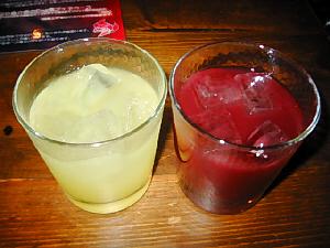 白っぽい液体のグラスと真っ赤な液体の入った2種類のグラス。片方はグレープフルーツでも入っているような色合いで、片方は?木のテーブルの上に並べられています。
