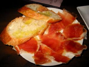 中くらいの白い丸皿に乗った生ハムとフランスパン、生ハムは削ぎ切りしたようで、値段の割には多めの枚数が。透明感の出た生ハムの色合いが綺麗です。