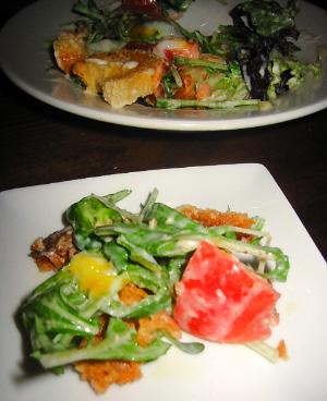 大きめの丸皿に盛られたサラダ、手前に白い四角い銘々皿が置いてあり、サラダが取り分けられて入っています。トマトや数種類のリーフ、白っぽいドレッシングが満遍なく絡んでいます。こんがり焼き色のついたパンが、香ばしそうです。
