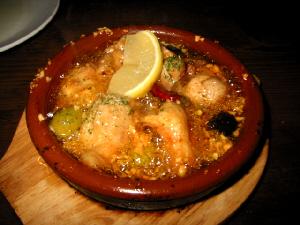 小さな土鍋に入れられたチキンのガーリックソテー。ぐつぐつ煮え立っているオリーブオイルが熱そう!鷹の爪の赤と、オリーブの緑、黒、そして上に乗ったレモンの黄色がアクセントになっています。細かい沢山見える粒は、ガーリックのようです。