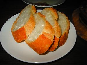 白い丸い更に入ったフランスパン4切れ。これだけで十分にお腹が満たせそうです。