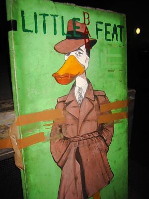 背丈ほどありそうなグリーン地の看板、トレンチコートを着て帽子を目深に被った男の口は、ペンギンの黄色いくちばしになっています。手はポケットに入れられ見えませんが、足はペンギンの足?
