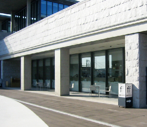 2階にある美術館のカフェ「ff」(フォルテシモ)。コンクリートの屋根と柱がアクセントの外観です。屋根の下にはテーブルと椅子が幾つか並べられています。カフェは前面ガラス張りで、中から神戸空港に降り立つ飛行機なども見ることが出来ます。