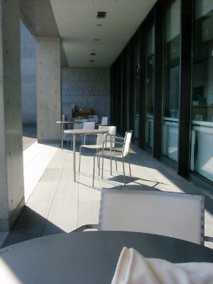 カフェのテラスの全体の風景。柱の影とお日様の日差しが差し込む部分とのコントラストが綺麗です。丸いテーブルと椅子の細い足が影絵のようになって、一枚の絵のような風景です。