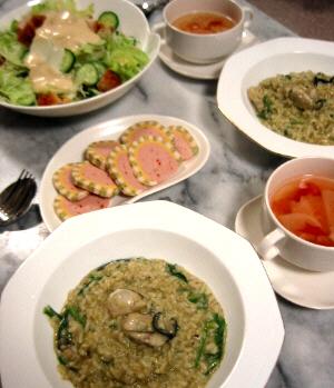 テーブルの上に、8角形のお皿の中にリゾット、四角いお皿の上に丸いカップスープが乗せられ、それらの向こう側に白い変形のお皿にカラフルな模様になったパテが。更にその向こうに白い大きいボウルに入ったサラダが並んでいます。