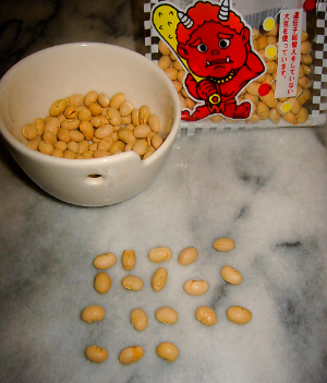 テーブルの上に白い小さな器の中に豆が入っています。豆の袋もすぐそばにあって、その袋には赤鬼のイラストが書いてあります。器の手前に前が並べられていて、数えると全部で18個あります。
