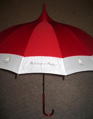 赤い傘なんですが、縁取りが幅広の白。そこに豚がジャンプしている絵と、ロゴが交互に入っています。傘を開いても、先端がとんがっていて、ちょっとレトロな雰囲気を持つ傘です。柄の部分も赤いべっ甲風の持ち手になっていて、斬新な感じもするのにレトロな雰囲気を持ち合わせた傘。